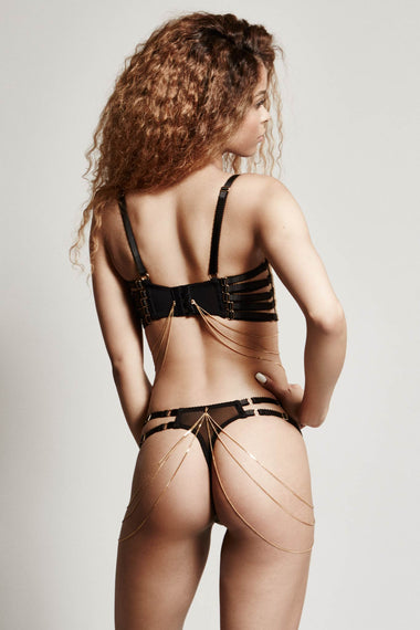 Edge o' Beyond Lingerie. The Valma thong is made with delicate gold thread, a rose floral design and bondage inspired strapping. An alternate back view including bra and 18k gold jewellery
