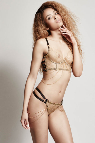 Edge o' Beyond Lingerie. The Valma thong is made with delicate gold thread, a rose floral design and bondage inspired strapping. Worn with matching bra