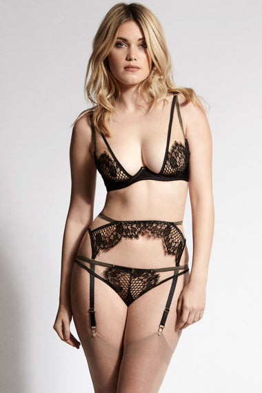 Edge o' Beyond Kathryn suspender belt features satin bound edges and fishnet-style lace with a scalloped finish for a unique lingerie look.