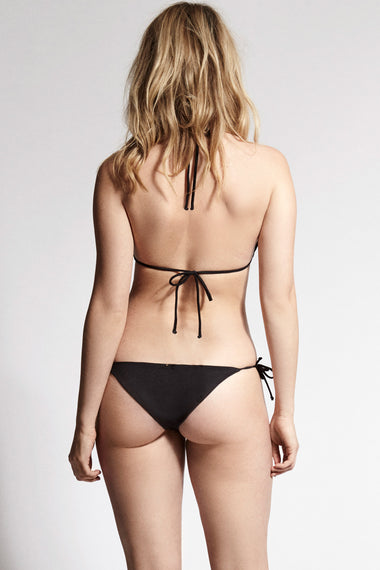 Black lace tie side bikini briefs. Nadine is the debut swimwear collection from luxury lingerie brand Edge o' Beyond. Back view worn with triangle bikini top