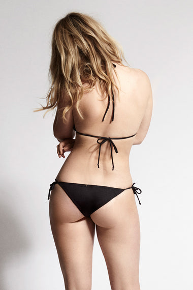Black lace tie side bikini briefs. Nadine is the debut swimwear collection from luxury lingerie brand Edge o' Beyond. Back view shown with triangle bikini top