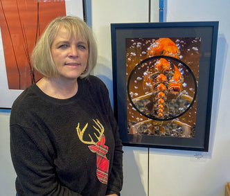 Debbie L Lind at an Art Show with her koi photo and fractal art.