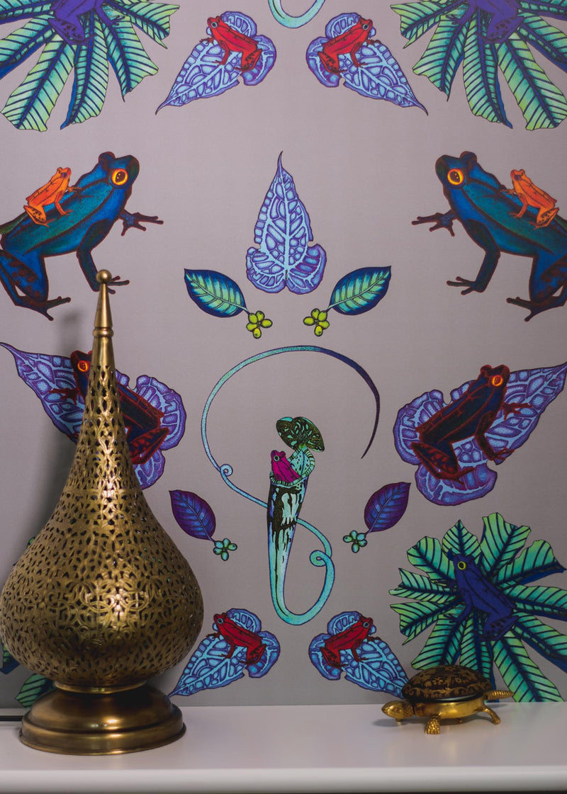 Frog wallpaper with brightly coloured frogs and leaves hung on a wall above mantlepiece