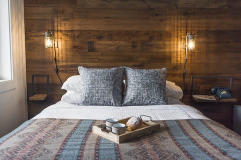 A hotel room at Snow Valley Lodging showing a reclaimed wood feature wall.
