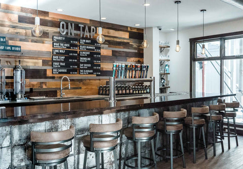 The bar & back bar at Fernie Brewing showing a reclaimed wood feature wall.