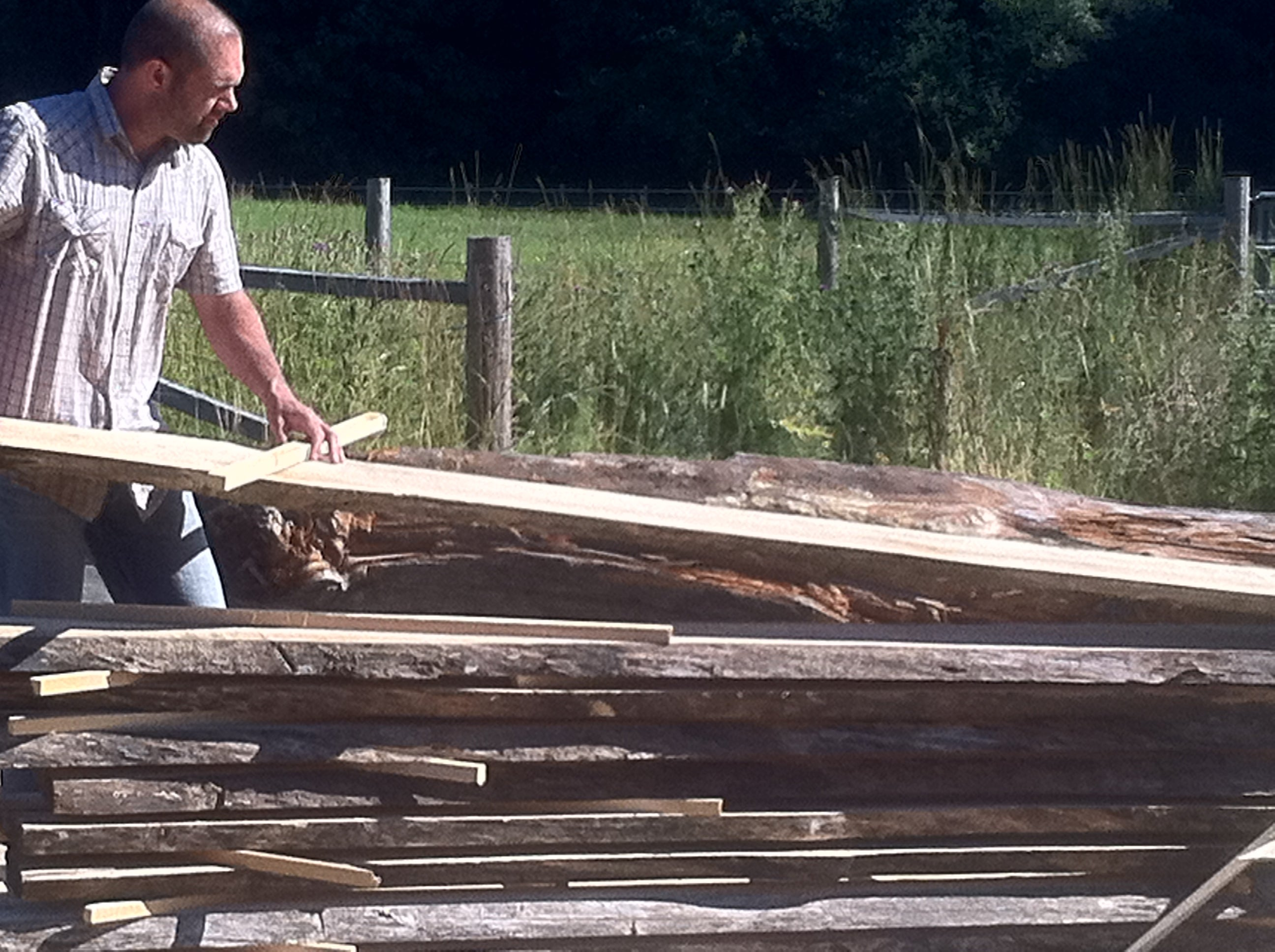 Owner Paul Arcoite inspecting reclaimed live edge wood planks to be used for feature walls and furniture.