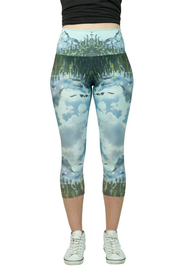 Capris legging printed with a landscape painting of Joffre Lakes by Heidi Denessen. Aqua blue, green, gold. Mountain, lake, trees. Made in Canada. Sustainable.