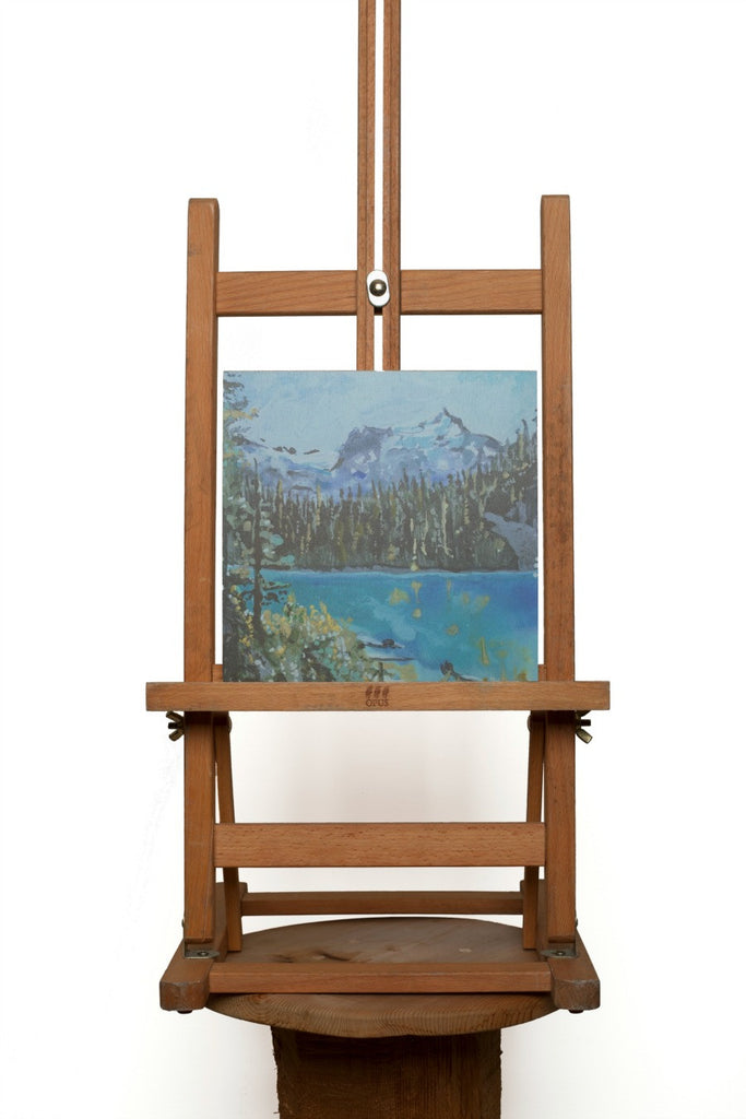 A print on a wood panel from an original painting by Heidi Denessen. Alpine lake and mountain.