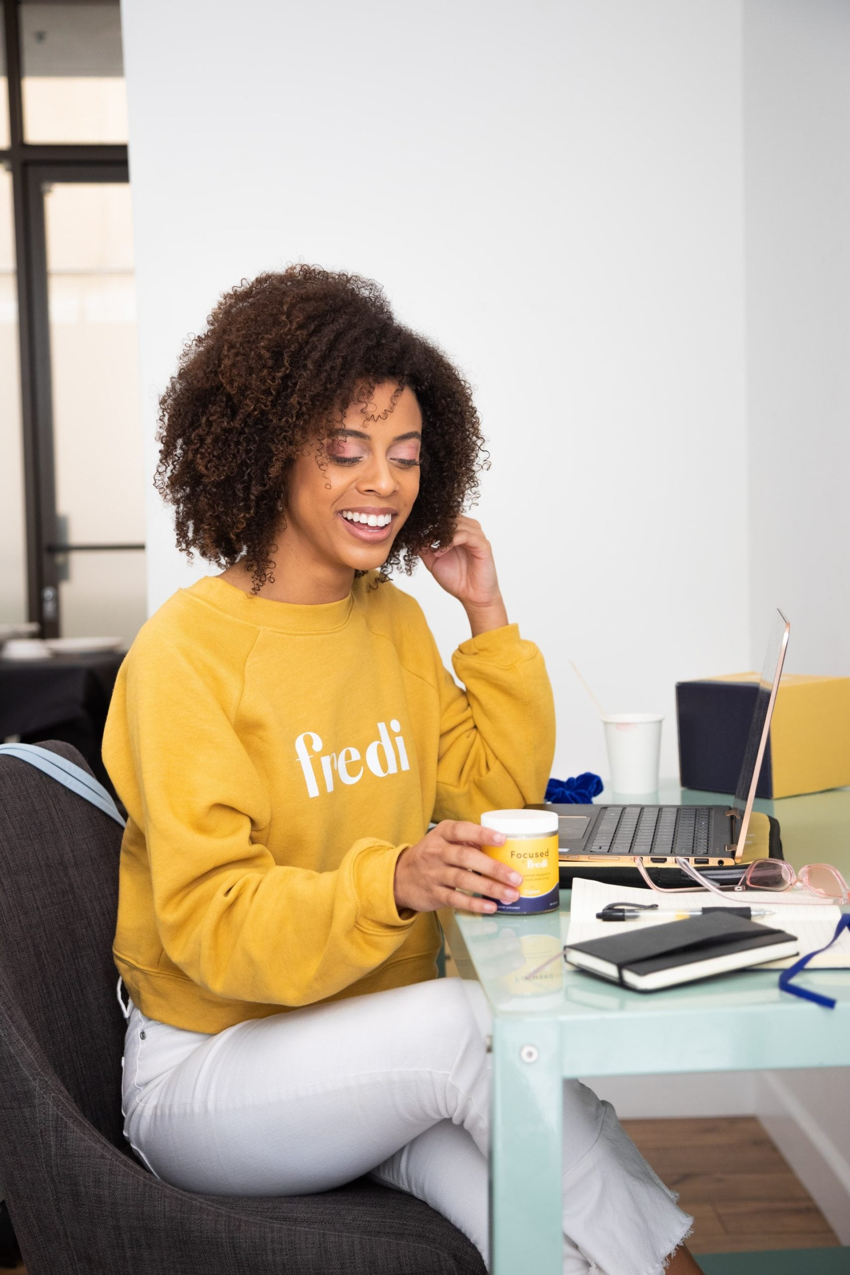 woman in yellow jumper smiling at coffee