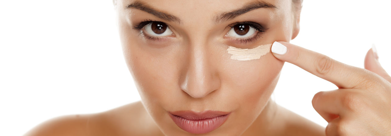 Female applying moisturizer to under eye