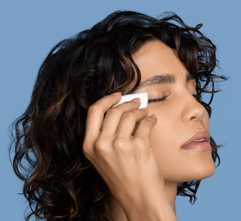 Female applying InstaNatural Rose Makeup Cleansing Balm to eye to remove her makeup