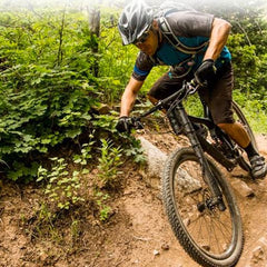 Man riding through mud gulley on Overmountain Trigger bike
