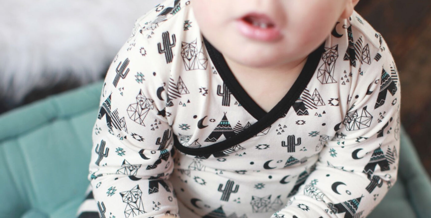 Infant in organic bamboo pajamas with desert print
