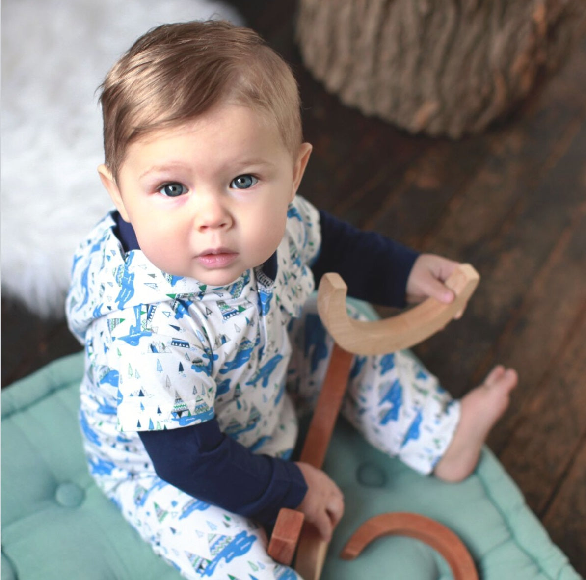Baby boy wearing hooded pajamas made with organic cotton