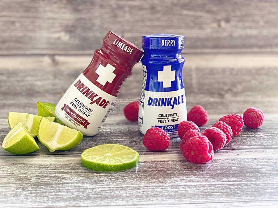 DrinkAde Prevention red bottle and Boost blue bottle with fresh limes and berries