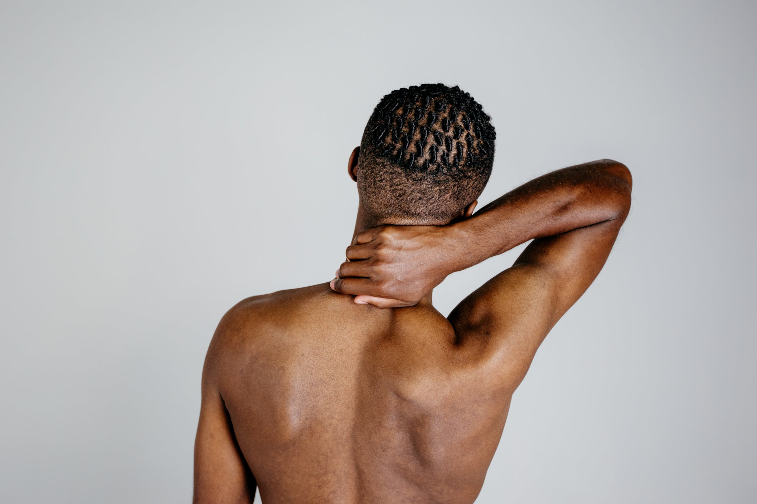 A man with cornrows faces away from the camera.