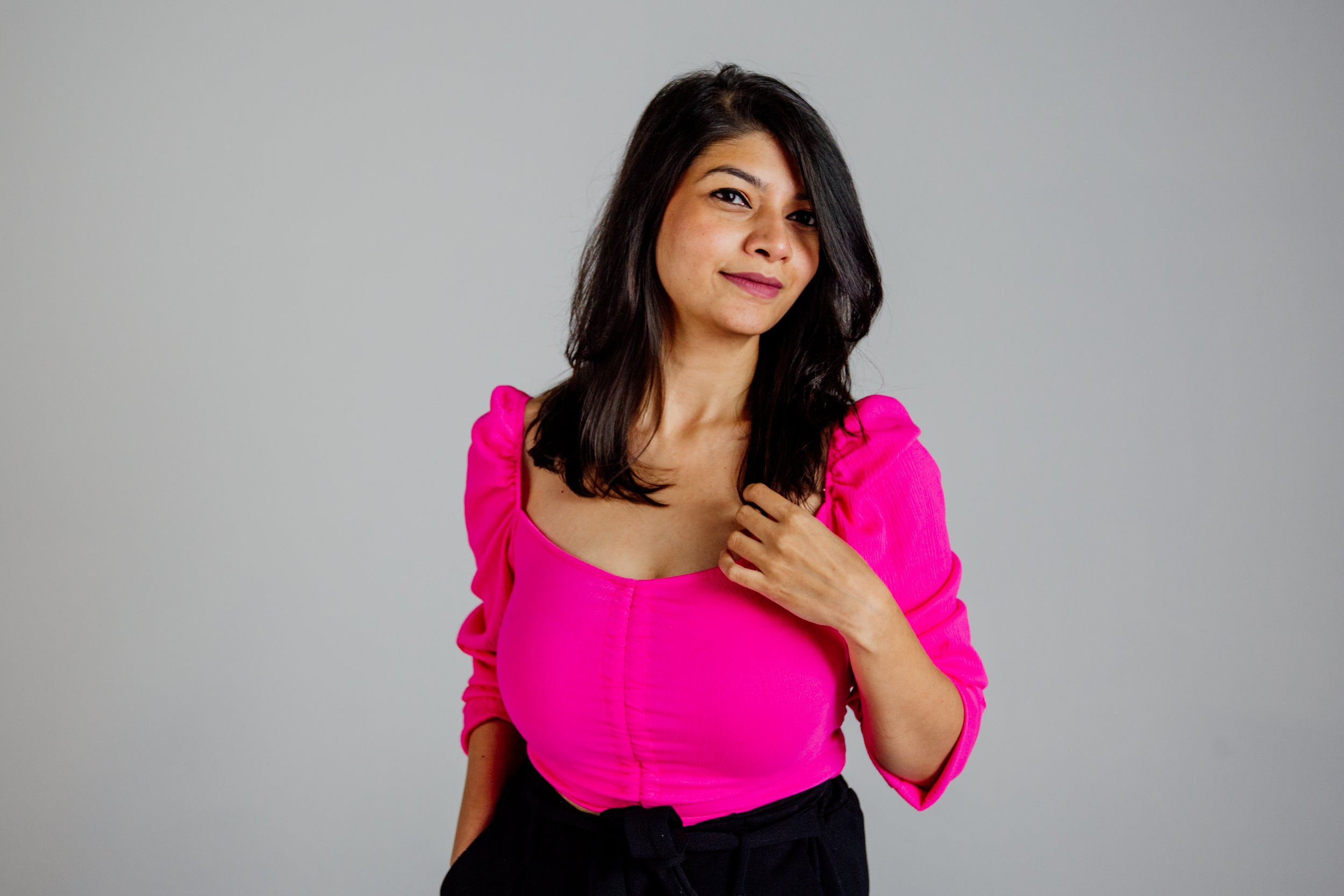A woman in a pink shirt poses.