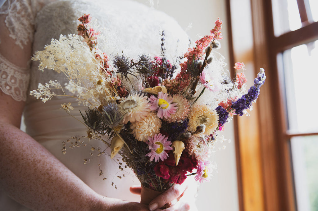 Close up shot of a dried wedding bouquet being held by a bride