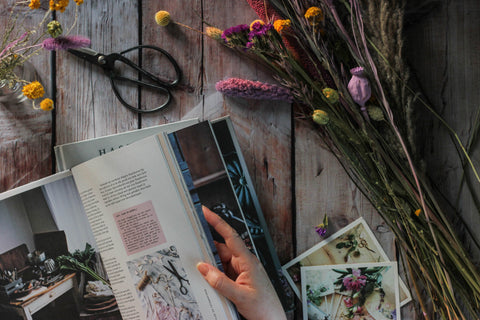 Hands looking through a book, surrounded by dried flowers