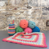 Crochet hooks, wool and a granny blanket on a table to advertise the beginners crochet course