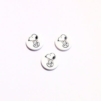 A round white button with Snoopy design printed in black on the front
