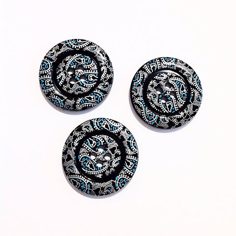 A black four holed button with a white and blue paisley pattern