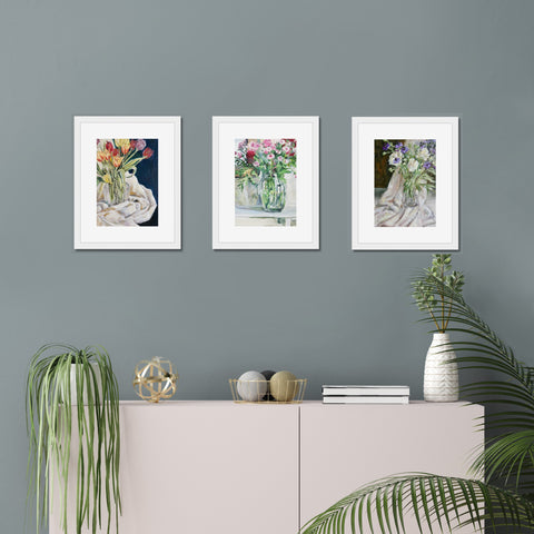 Three giclee art prints of oil paintings of tulips, nigella, peonies and pink flowes in vases, framed and hung on a wall