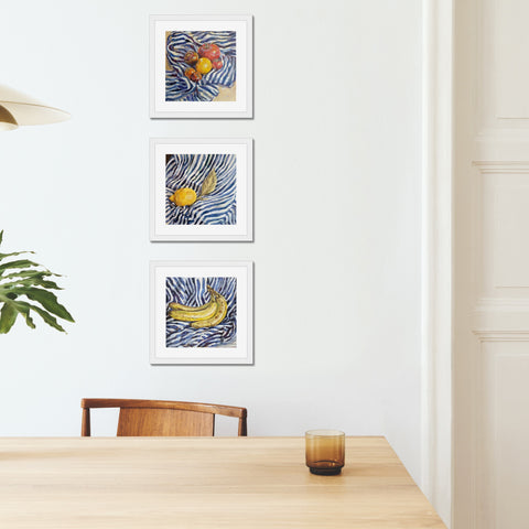 Three art prints of oil paintings by artist Harriet Lawless of bananas, tomatoes and a lemon on a blue and white stripey cloth, framed and hung on a wall.