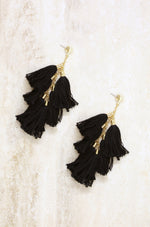 Daydreamer Tassel Earrings in Black and Gold on slate background