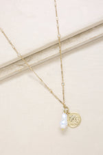 Trusty Trinkets Pearl and Coin 18k Gold Plated Necklace on slate background