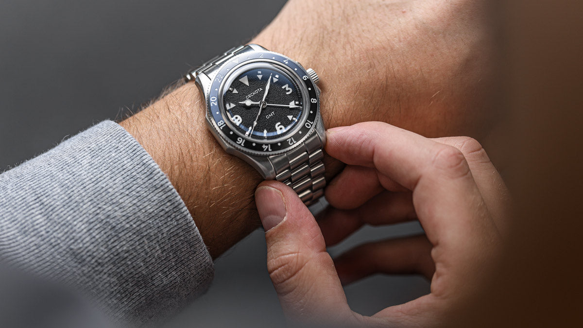 Lifestyle watch photography of the Geckota GMT Blue and Black Bezel Watch on wrist.