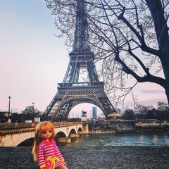 Lottie doll in Paris with the Eiffel Tower in the background