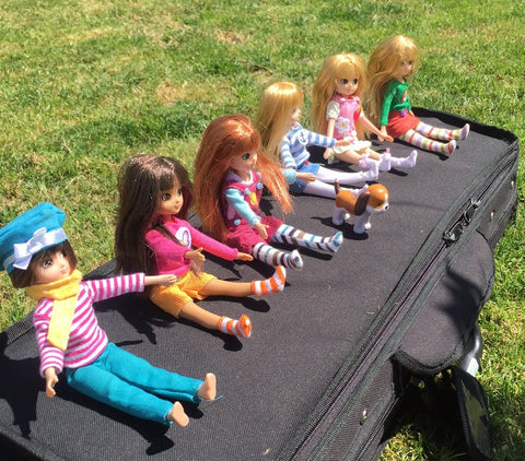 bunch of lottie dolls sitting on a violin case