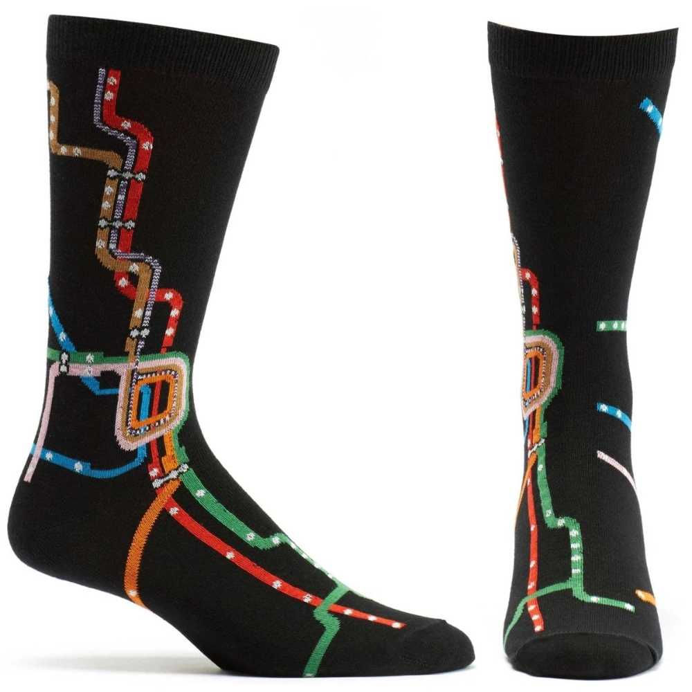 image of white woman with brown hair wearing a sleeveless white top and a pink and green gauzy scarf around her neck