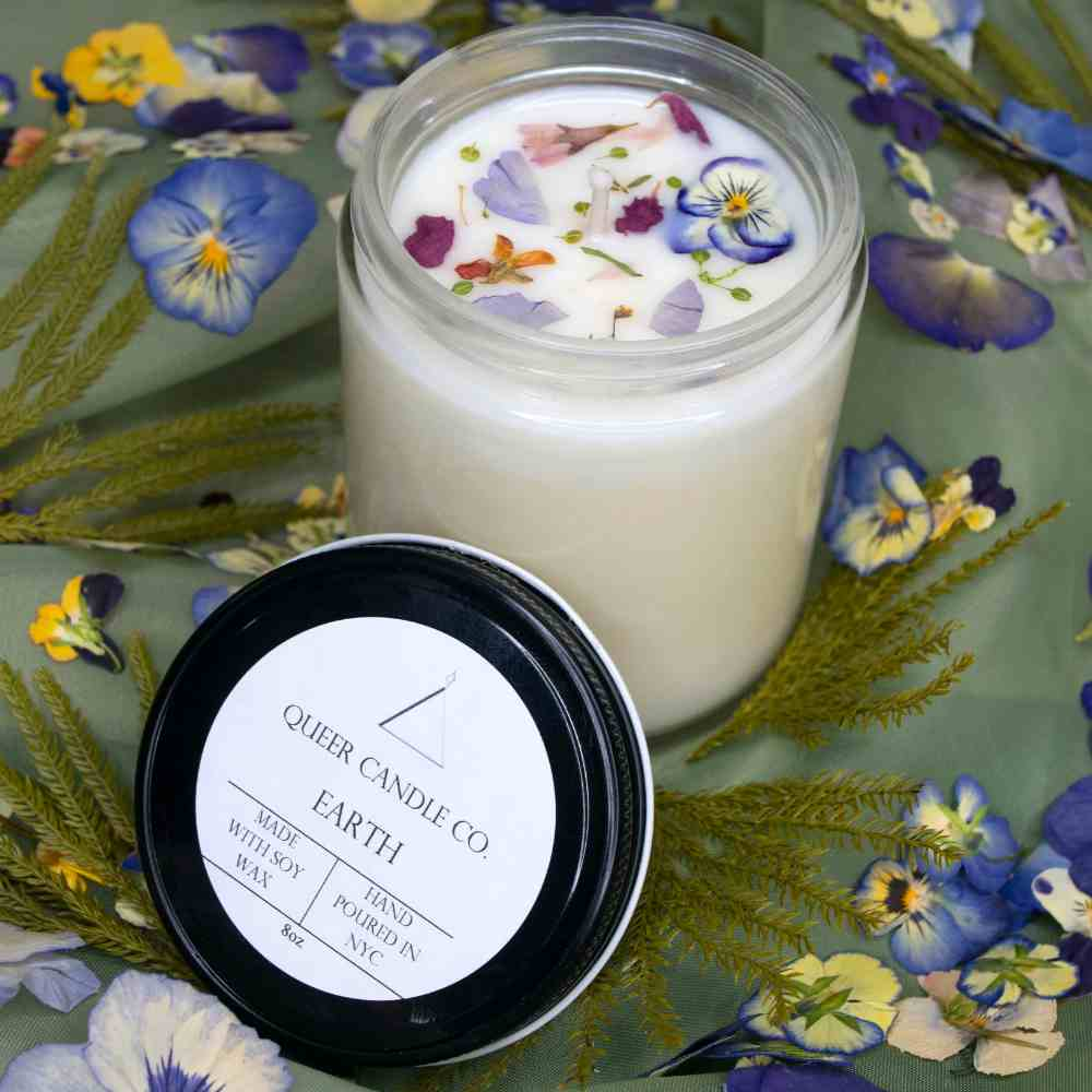image of white jar candle in front of a grey pot with a plant in it