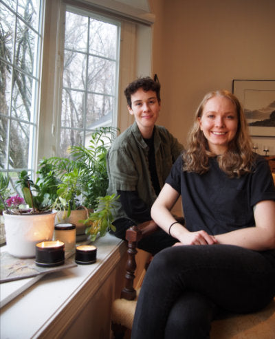 image of two people, owners of queer candle company, sitting in front of a window with samples of their candles on the surface next to them
