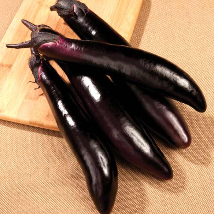 image of four long dark purple eggplants grouped on a surface, partially on a wooden cutting board
