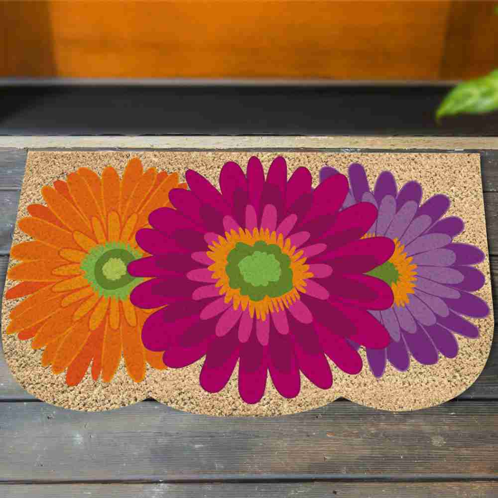 Image of the gerbera daisy coir mat on a wood deck in front of a door.