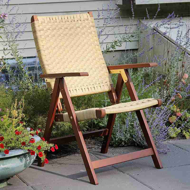 brown wooden folding chair with woven back and seat, sitting on patio with plants in background