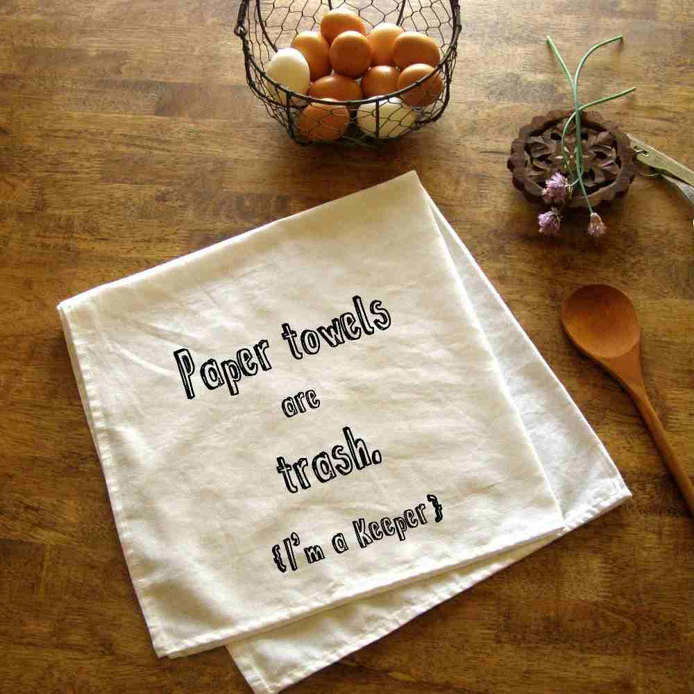 "white towel silk screen with ""paper towels are trash I'm a keeper"" in black, on wooden countertop"