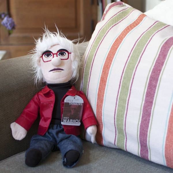 image of andy warhol doll with red jacket, blue jeans, black turtleneck, red eyeglasses and a shock of white hair