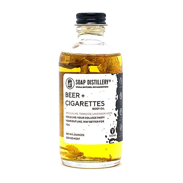 Glass bottle with black and white label and yellow body oil inside