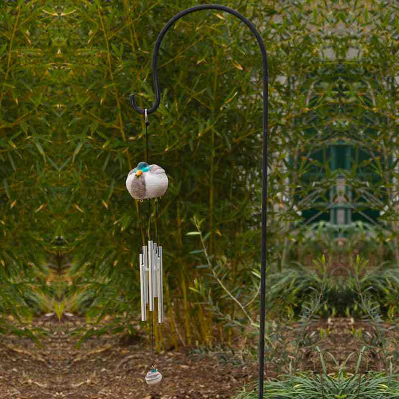 black iron shepherd's hook with bird wind chime hanging from it and bamboo plants in the background