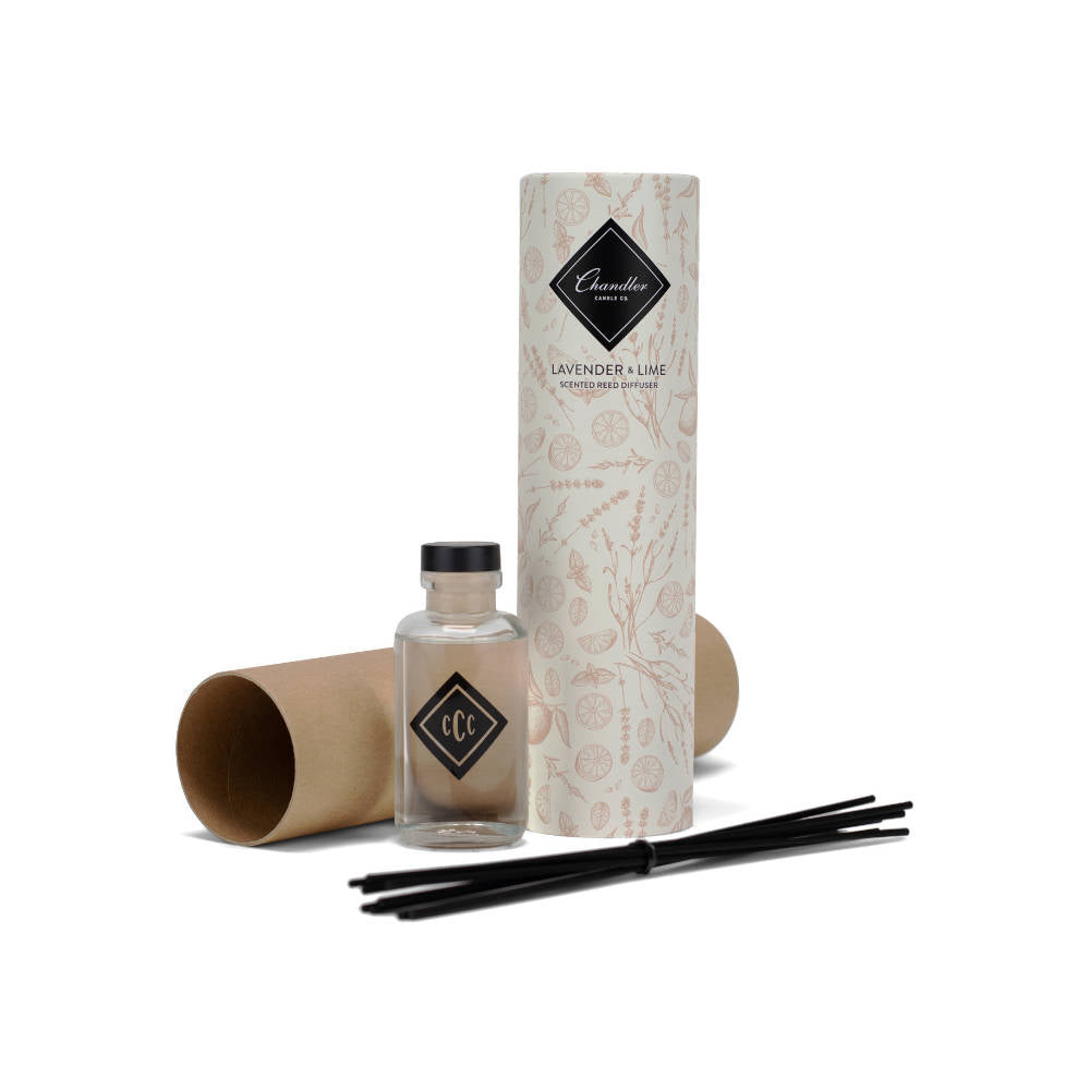 glass bottle with reed diffusers, next to round cardboard tube container with Chandler logo