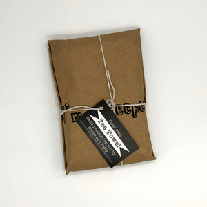 towel packaged in brown paper wrapped with string and black and white price tag
