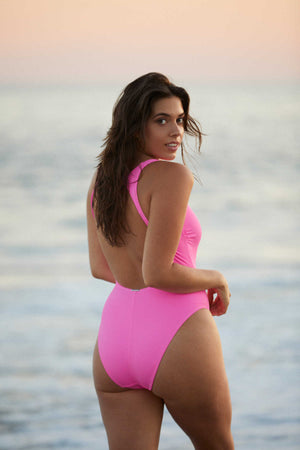woman on beach in a pink one piece swimsuit