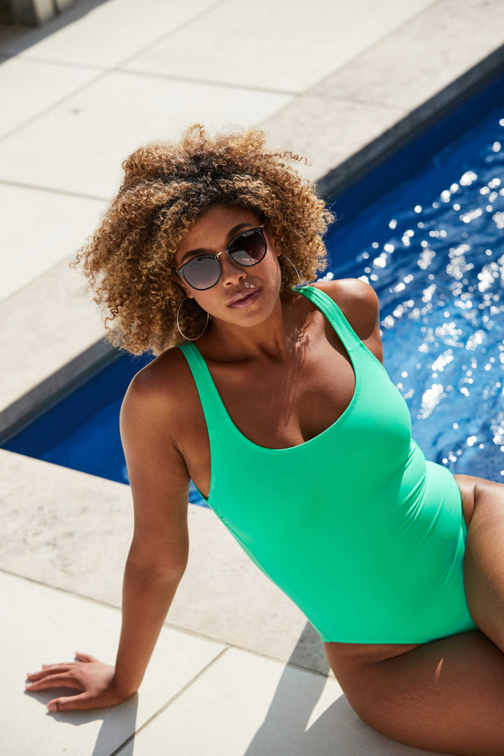 woman sitting near pool wearing a green one piece swimsuit