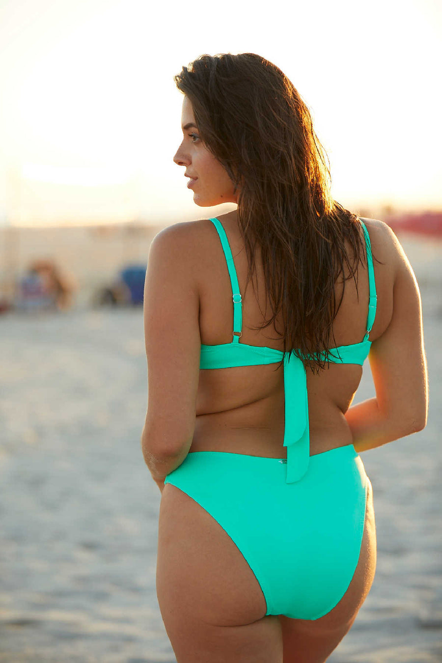 Woman standing on beach wearing a two piece green bikini