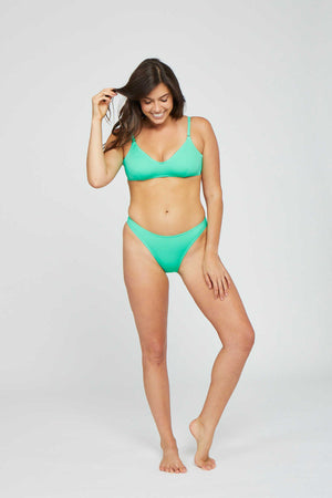 Woman standing wearing a green two piece bikini