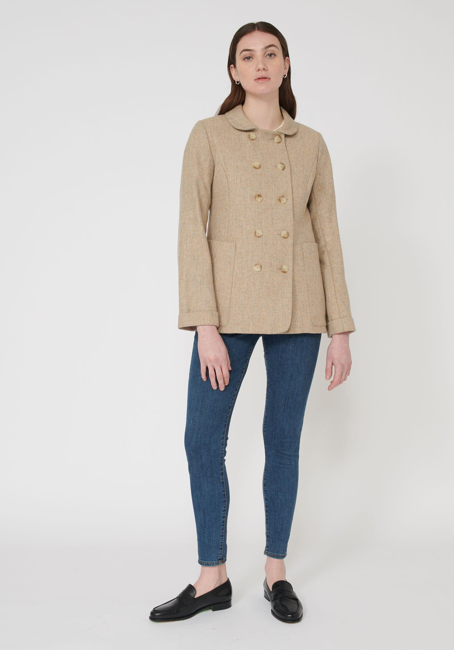 A casual, slightly oversized jacket featuring a rounded collar, double-breasted buttons, and large pockets, the Artist jacket pairs perfectly with jeans.  Made in our London workshop from a lightweight wool, the perfect layering piece for those cooler Spring days. Artist Jacket | Pebble Peach Wool front view